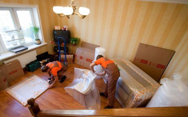 Грузчики собирают и упаковывают вещи для переезда